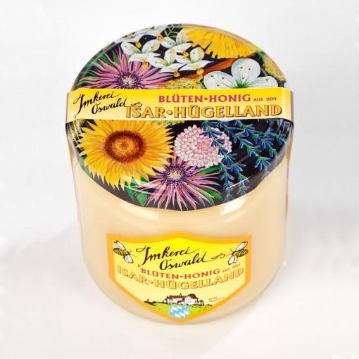 Honig, ein Glas Blütenhonig mit dem gelben, hofeigenen Etikett von Imkerei Oswald und dem bunten Blütendeckel, der ein Aquarell von den wichtigsten Trachtpflanzen zeigt.