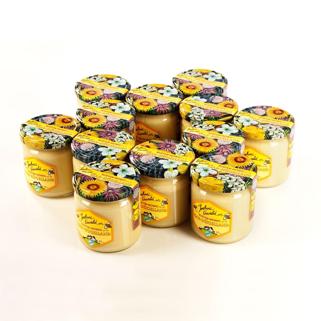Bio-Honig München: Zwölf bunte Gläser Bienenhonig, die in Stern- bzw. Blumenform geometrisch angeordnet sind.