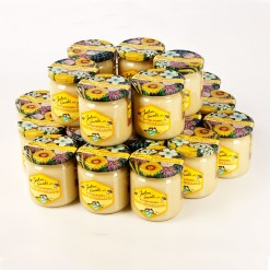 HONIG FÜR KLEINKINDER; Ein Produktfoto, auf dem vierundzwanzig bunte Honiggläser mit bunten Blütendeckel in einer zweistöckigen Rundpyramide für dem Honigversand nett arrangiert sind.