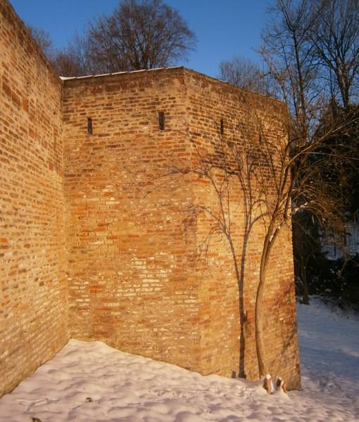 Am verscheiten Burghang ist ein ziegelgemauerter Torvorbau mit Schießscharten zu sehen, und ein Teil der Wehrmauer. Das warme, verwaschene Rot der Ziegel gibt einen angenehmen Kontrast zum tiefen Kobaltblau des Himmels.