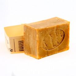 Eine quadratische Naturseife aus Lorbeer und Olive mit einem Herstellerstempel mit arabischen Schriftzeichen aus Aleppo.
