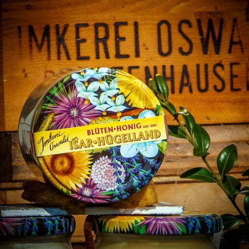 Ein Honigglas mit buntem Blütendeckel und Siegelstreifen. Auf dem Deckel sind in bunten Farben die wichtigsten Bienenpflanzen gemalt: Wiesenflockenblume, Robinie, Löwenzahn, Apfelblüte, Haselnuss, Sonnenblume, Rotklee, Palmkätzchen und Lavendel.