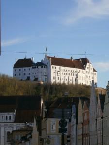 MET VON FAMILIE OSWALD Eine weiße Burg auf einem Berg im milden Abendsonnenlicht.