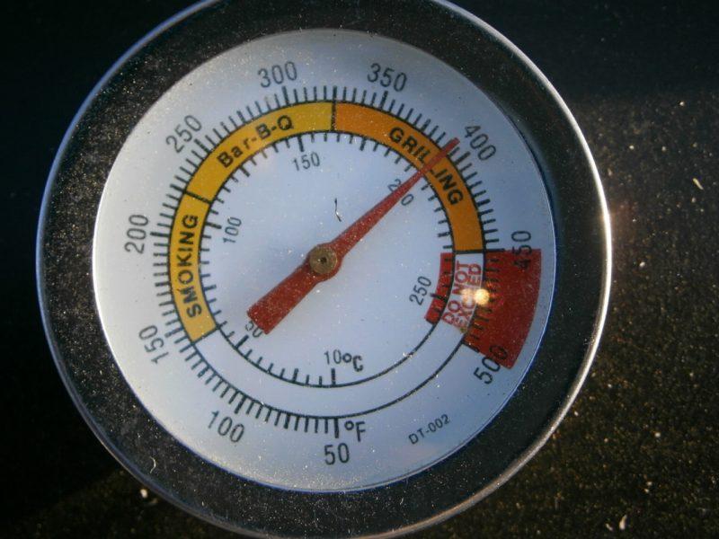 Ein Grillthermometer an einem modernen Smoked Meat Grill. Der Zeiger steht auf 400° und zeigt an, dass jetzt das Fleisch fertig ist und mit Alpensalz gewürzt werden kann.