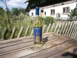 Eine Flasche Met Linde Lindenmet Honigwein aus lieblichem Lindenhonig mit blau-goldenem Etikett, fotografiert im freien im Bienengarten auf dem historischen Bienenhof der Familie Oswald.