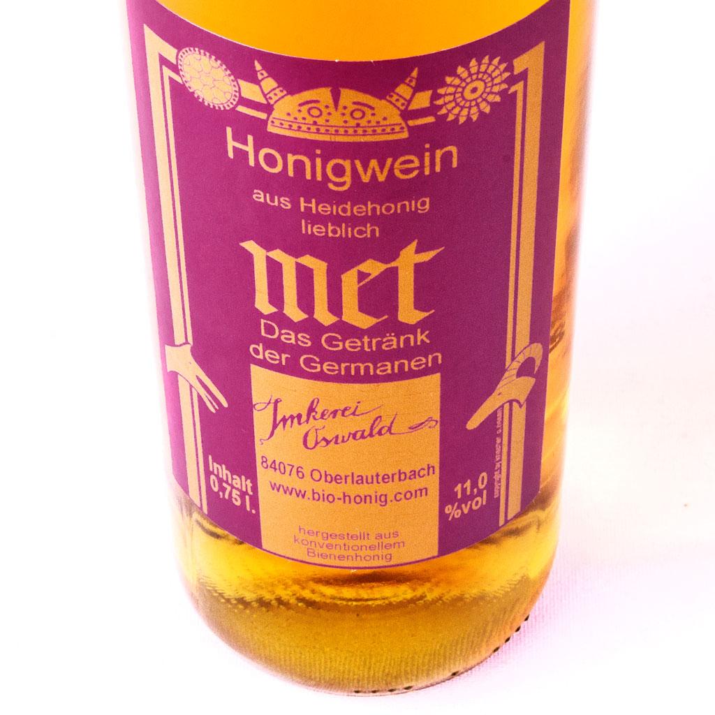 Germanenmet Honigwein aus lieblichem Heidehonig von warmer, tiefgoldener Farbe und magentafarbenem Etikett.