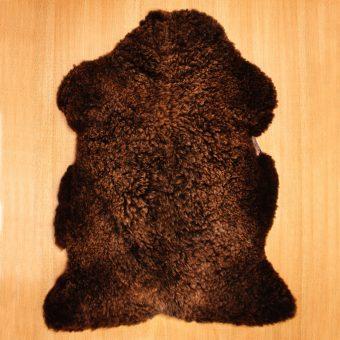 Ein braunes Lammfell liegt ausgebreitet mit der Fellseite nach oben auf einem Tisch.