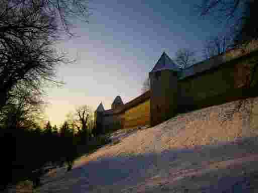 Romantische Winterstimmungsbild der Burg Trausnitz in Niederbayern. Steil erhebt sich ein steiler, verschneiter Hang, der von einer sehr hohen Wehrmauer bekrönt ist. Es sind noch drei spitzdachige, hexagonale Wachtürme zu sehen, die die Wehrmauer flankieren.