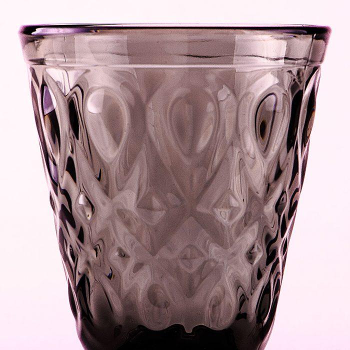 Weinglas schwarz wor weißem Hintergrund.