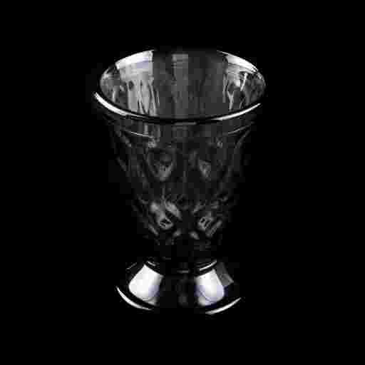 Weinglas schwarz mit Edelstein Prägung vor schwarzem Hintergrund.