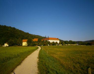 Schön gelegen an der Sonnenseite eines bewaldeten Tals liegt das alte Kloster, umgeben von ökologischen Viehweiden und Lindenbäumen. Die Barockanlage ist in einem Winkel von 120° gebaut, ähnlich wie die Bienenzelle.