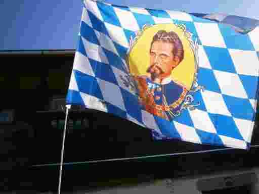Das Portrait König Ludwig des Zweiten als Wappenbild auf einer bayerischen Rautenfahne. Das Wappenmedaillon ist mit silbernem Rahmenwerk eingefaßt. Die Hintergrundfarbe ist gelb. Der bayerische König trät seine blaue königliche Uniform. Dahinter ist das historische Bauernhaus von Hans Georg und Ruth Oswald zu sehen.