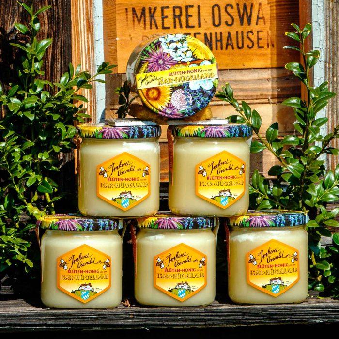 """HONIG, BLÜTENPOLLEN, MARZIPAN; Naturhonig Honigpyramide von sechs Mal fünfhundert Gramm Biohonig von heller Honigfarbe. Die Gläser stehen auf dem Flugbrett von der Zuchtstation der Hallertauer Biene zwischen zwei Buchssträußen. Hinterr den Gläsern sieht man durch die Fenster des Bienenhauses einen Bienenkasten mit dem Brandstempel """"Imkerei Oswald Pfeffenhausen""""."""
