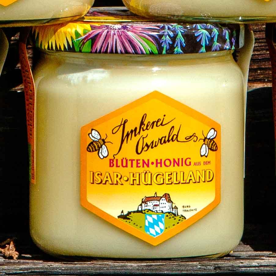 Ein Glas guten Honigs von Imkerei Oswald aus dem Isar-Hügelland. Das Glas ist im Freien vor dem Bienenhaus fotografiert.