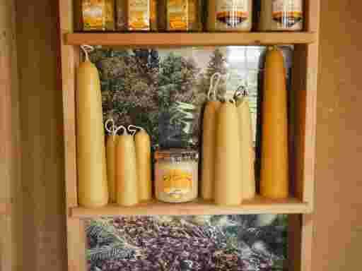 Stumpenkerzen in verschiedenen Größen, links neben dem Honigglas eine kleine Stumpenkerze.
