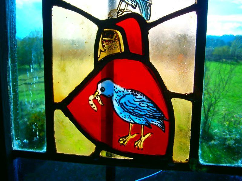 Ein Wappenfenster in den Farben rot und blau.