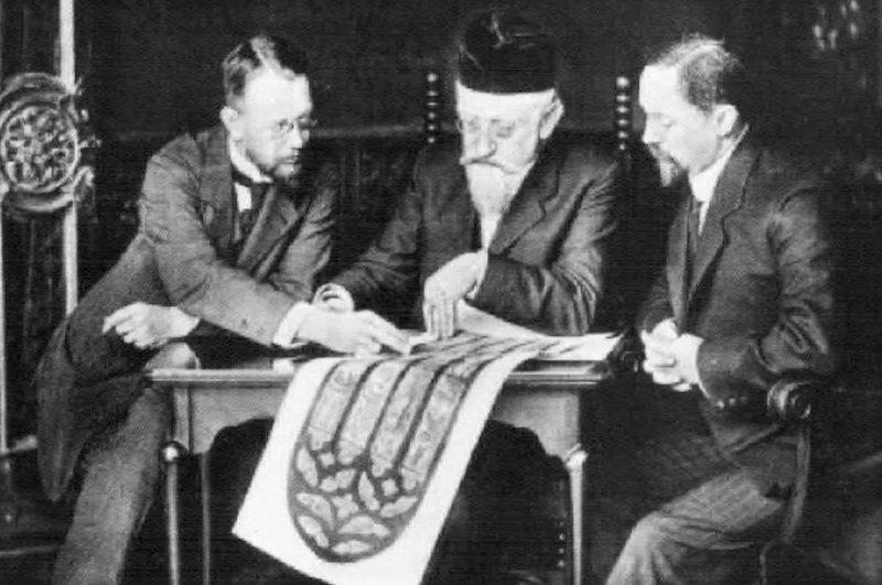 Franz Xaver Zettler sitzt mit seinen beiden Söhnen am Tisch, eine Zeichnung eines gotischen Maßwerkfensters betrachtend.