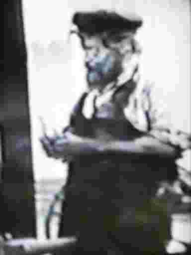 Ein Schlosser in typischer Arbeitskleidung, Schürze und Mütze.