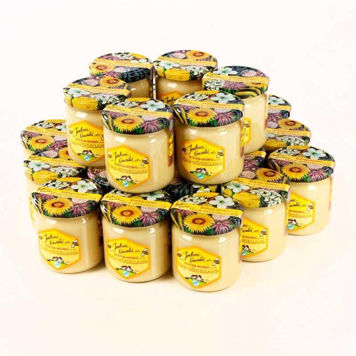 Ein Produktfoto, auf dem vierundzwanzig bunte Honiggläser mit bunten Blütendeckel in einer zweistöckigen Rundpyramide für dem Honigversand nett arrangiert sind.