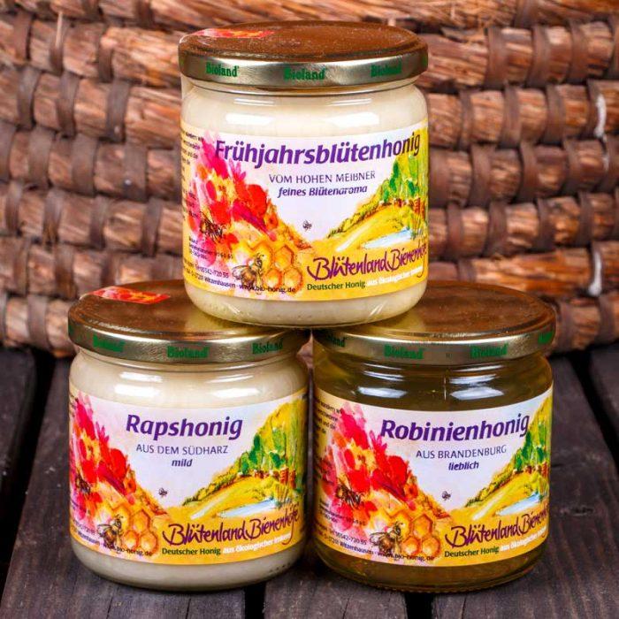 Jeweils ein Glas flüssger Honig, Creme-Honig, und zartschmelzender Honig in Form einer Honigpyramide vor einem Bienenkorb.