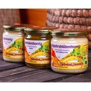 Ein Honigset aus milden Honigsorten fürs leckere Honig-Frühstück. Abgebildet ist ein 500g Glas Rapshonig, ein 500g Glass Robinienhonig und ein 500g Glass Frühjahrsblütenhonig in eine Reihe vor einem Bienenkorb.