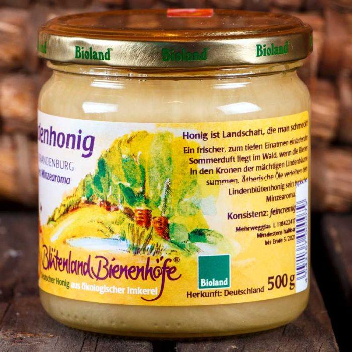 Detailaufnahme vom Etikett des fünfhundert Gramm Honig-Glases mit Lindenhonig. Dort ist der Schriftzug Blütenland Bienenhöfe in lila Schreibschrift zu lesen, und ein quadratisches Bioland Logo in grün und weiss.