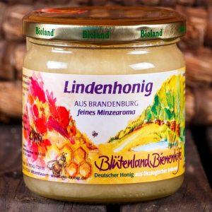 Ein Glas Deutscher Honig aus Bio-Imkerei von der Linde mit buntem Etikett von Heike Appels Bioland Imkerei Blütenland Bienenhöfe. Auf dem Etikett ist ein Aquarell zu sehen, das zwei handgezeichnete Bienen zeigt.