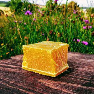 Ein Würfel von gelbem BIO-Bienenwachs aus eigener Imkerei.