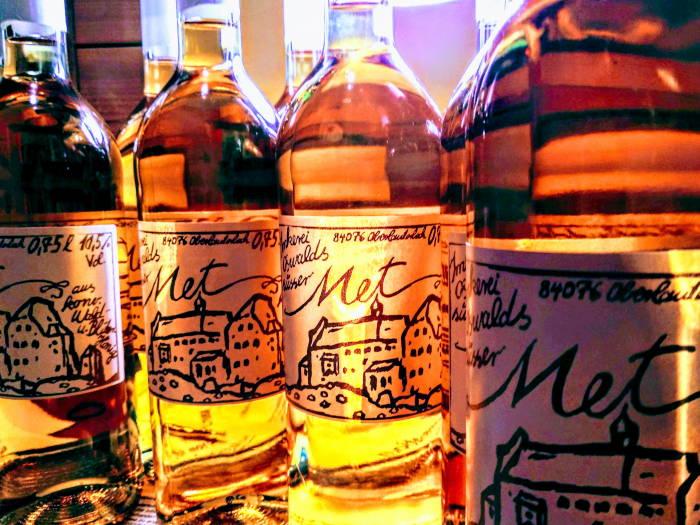 Einige Flaschen Honigwein beziehungsweise Met leuchten goldgelb im Licht der Lampe.