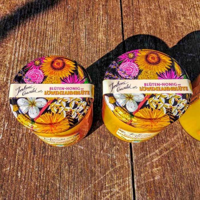 Zwei Honiggläser von oben mit Deckeln, die buntes Blüten-Dekor zeigen.