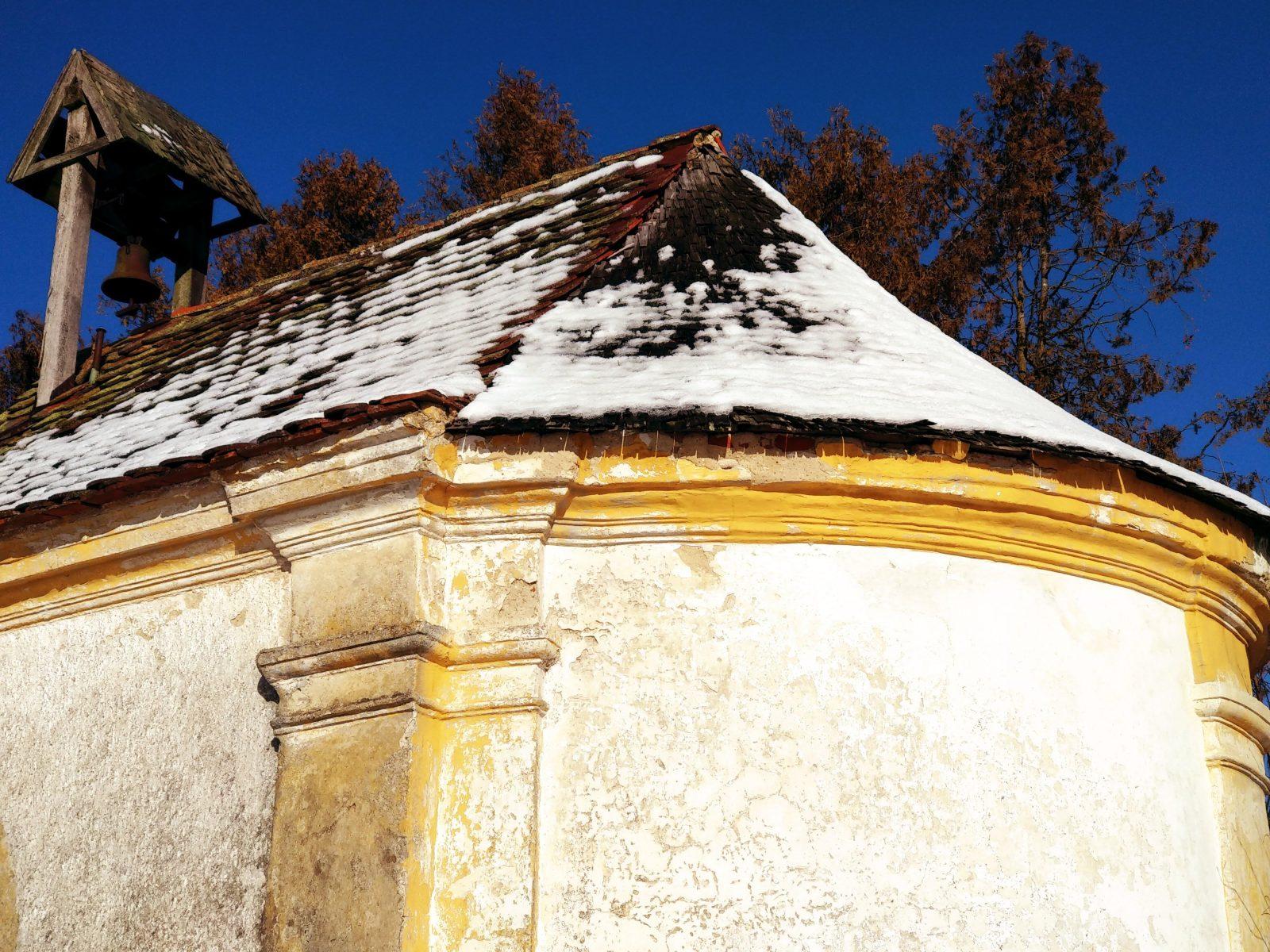 Alte Kapelle mit Glockenturm im Schnee.