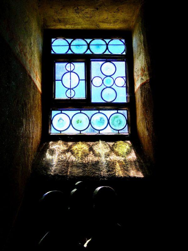 Ein altes Holzfenster mit mittelalterlichen Butzenscheiben und einem barocken Holzstuhl.