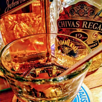 Ein Glas Whisky, dahinter zwei Whisky-Flaschen Scotch.