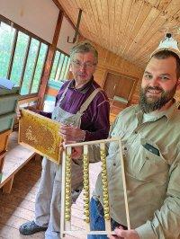 Zwei Bienenzüchter in einem Bienenhaus oder Bienenzüchtungsstation halten eine Zuchtwabe und einen Zuchtrahmen in Händen.