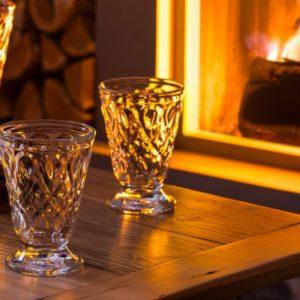Zwei romantische Gläser in florentinischem Design stehen auf einer Holztischplatte neben einem aufgeschlagenem Buch.