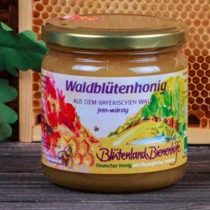 Foto eines Glases Bienenhonig auf einem verwitterten Brett stehend. Im Hintergrund eine Honigwabe der Imkerei Oswald und Eichenlaub.